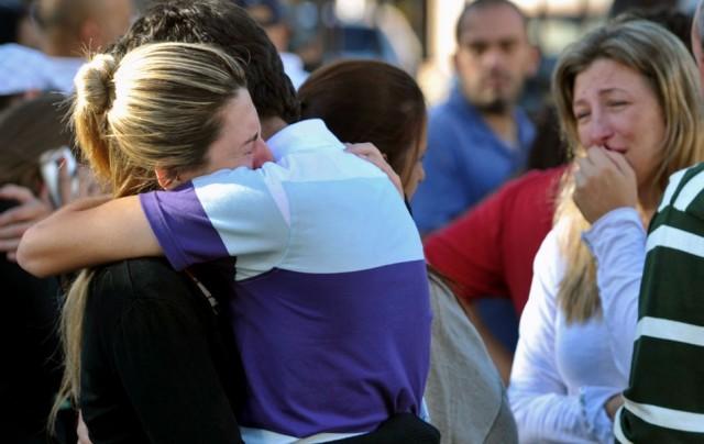 Familiares de vítimas se abraçam em frente a boate Kiss, em Santa Maria. Foto:  AP