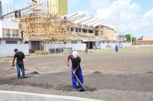 Operários trabalhando na colocação de estrutura de concreto e na drenagem do campo