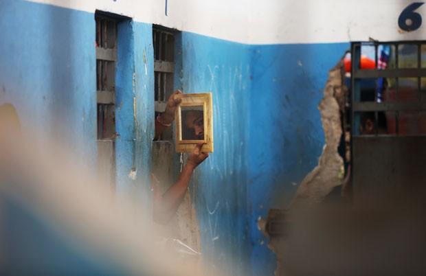Presidiário usa um espelho para observar visitantes que adentram o presídio de Pedrinhas (Foto: Mario Tama/Getty Images)