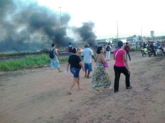 Pessoas descendodos ônibus e caminhando pea BR